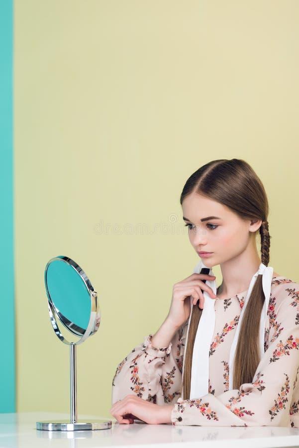 κορίτσι εφήβων που κοιτάζει στον καθρέφτη και σχετικά με τις πλεξούδες της στοκ εικόνα