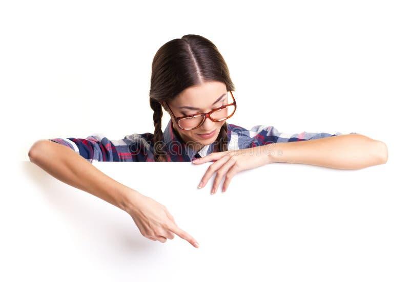 Κορίτσι εφήβων που παρουσιάζει στον κενό λευκό πίνακα στοκ εικόνες
