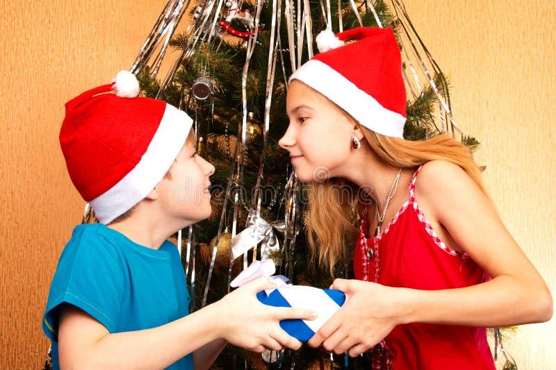 Κορίτσι εφήβων που προσπαθεί κοροϊδευτικά να πάρει μαζί ένα χριστουγεννιάτικο δώρο από τον αδελφό της στοκ φωτογραφία