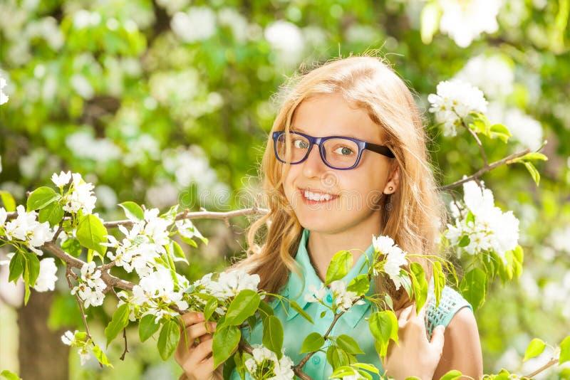 Κορίτσι εφήβων που φορά τα γυαλιά κοντά στα άσπρα λουλούδια στοκ φωτογραφίες με δικαίωμα ελεύθερης χρήσης
