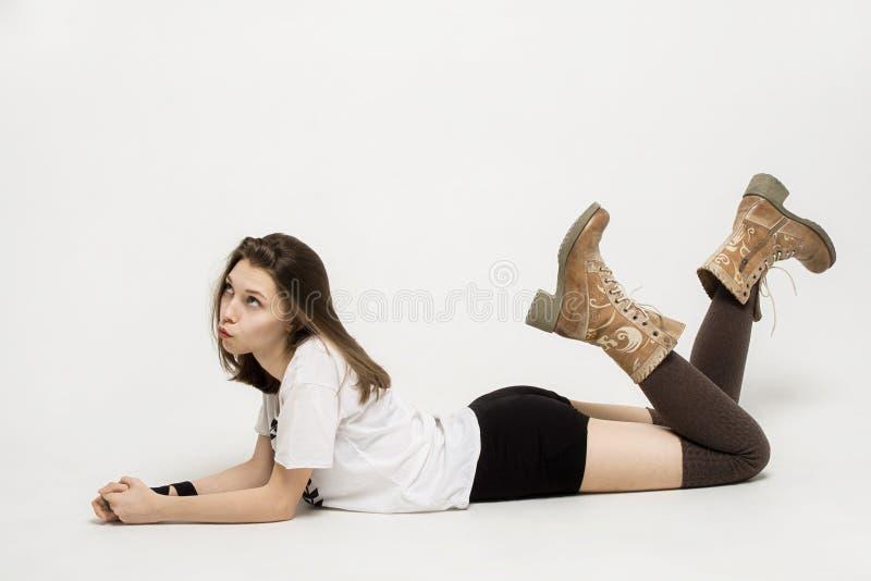 Κορίτσι εφήβων στην άσπρη μπλούζα, τις μπότες και τα μαύρα σορτς που βρίσκονται στο πάτωμα και που ανατρέχουν στοκ εικόνες με δικαίωμα ελεύθερης χρήσης