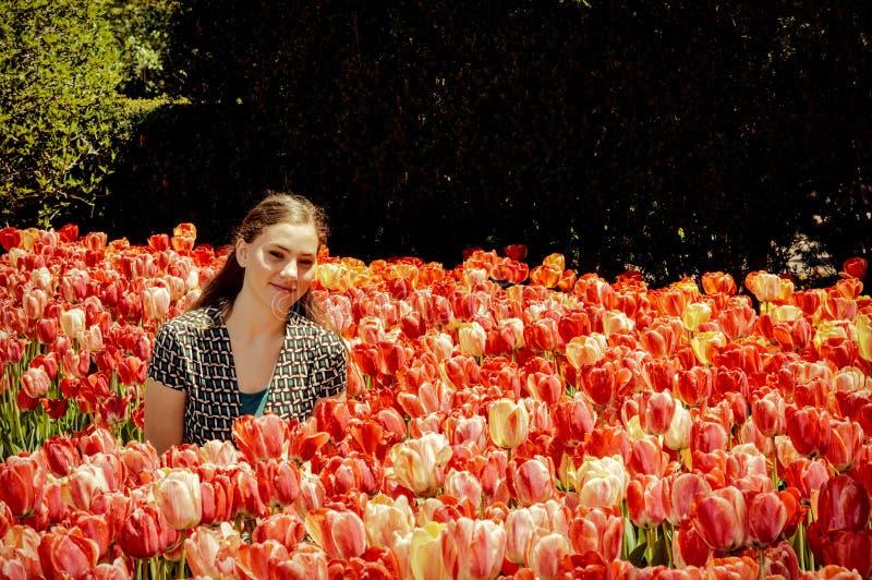 Κορίτσι εφήβων στον κήπο λουλουδιών τουλιπών στοκ φωτογραφία