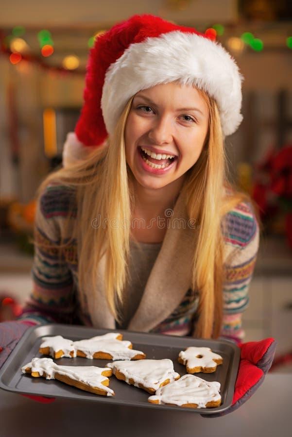 Κορίτσι εφήβων στο καπέλο santa που παρουσιάζει τηγάνι των μπισκότων στοκ φωτογραφία με δικαίωμα ελεύθερης χρήσης