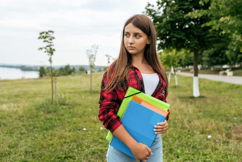 Κορίτσι εφήβων το καλοκαίρι στο πάρκο, σε ένα κόκκινο πουκάμισο στα χέρια της που κρατούν τα σημειωματάρια και τις σημειώσεις στο στοκ εικόνα με δικαίωμα ελεύθερης χρήσης