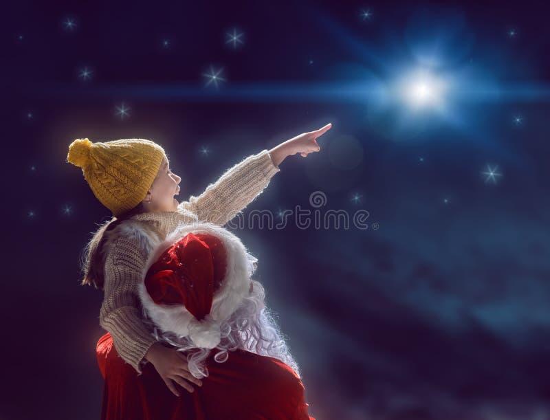 Κορίτσι και Άγιος Βασίλης που εξετάζουν το αστέρι Χριστουγέννων στοκ εικόνα με δικαίωμα ελεύθερης χρήσης
