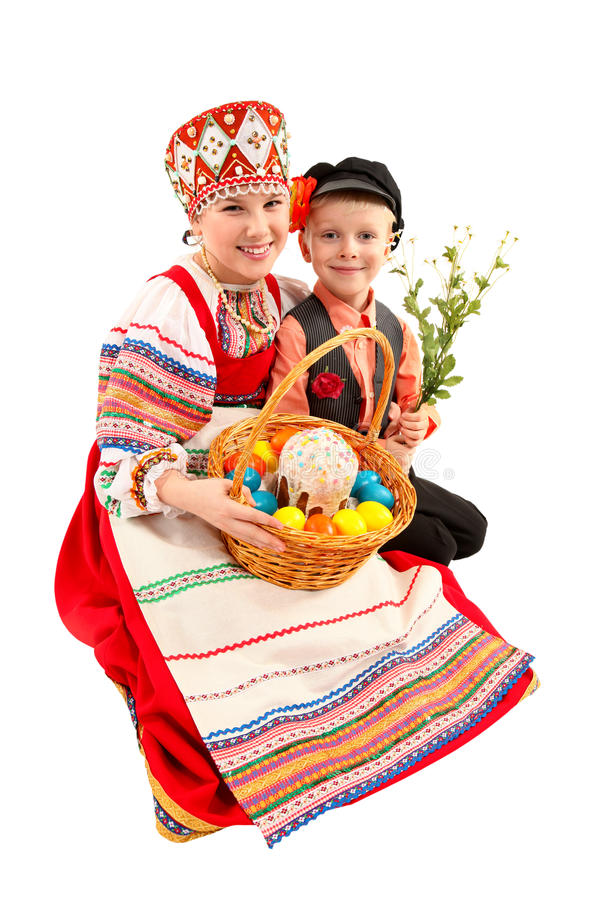 Κορίτσι και αγόρι με τα αυγά Πάσχας και ένα κέικ διακοπών στοκ εικόνα