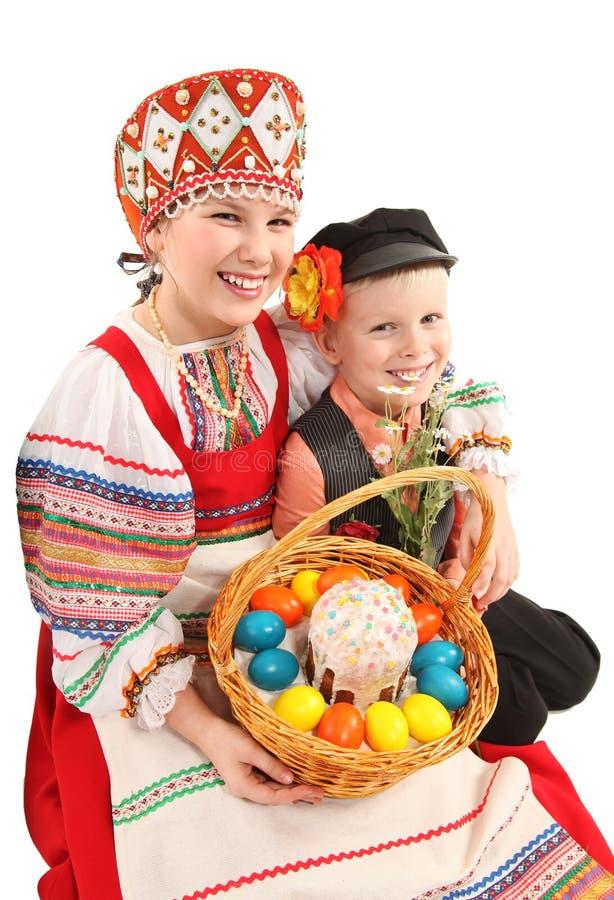 Κορίτσι και αγόρι με τα αυγά Πάσχας και ένα κέικ διακοπών στοκ φωτογραφία με δικαίωμα ελεύθερης χρήσης