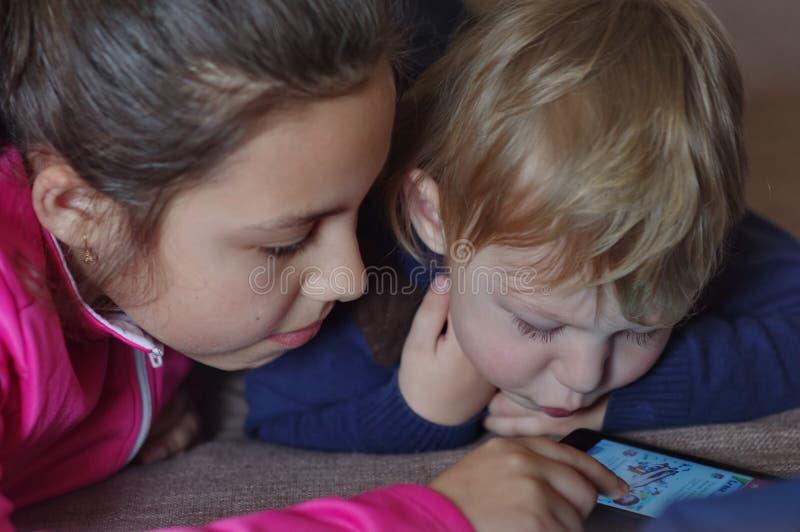 Κορίτσι και αγόρι που κοιτάζουν βιαστικά το Διαδίκτυο στοκ φωτογραφία