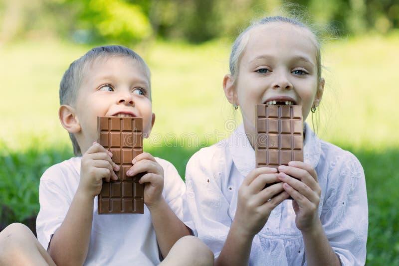 Κορίτσι και αγόρι που τρώνε τη σοκολάτα υπαίθρια στοκ φωτογραφία με δικαίωμα ελεύθερης χρήσης