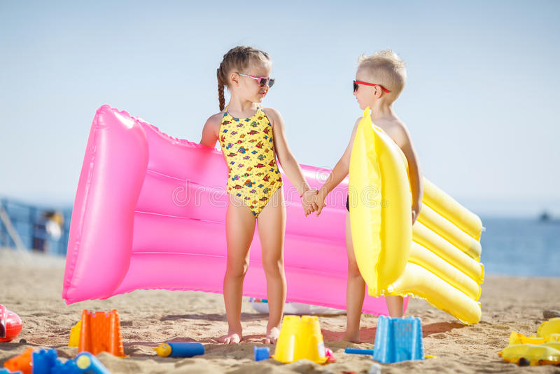 Κορίτσι και αγόρι στην παραλία με το διογκώσιμο στρώμα στοκ φωτογραφία