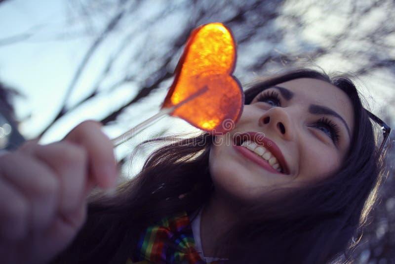 Κορίτσι και καραμέλα στη μορφή μιας καρδιάς στοκ εικόνες με δικαίωμα ελεύθερης χρήσης