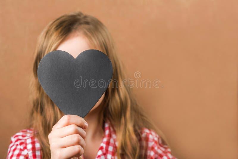 Κορίτσι και μαύρη καρδιά πλακών Το κορίτσι χτίζει μια φυσιογνωμία, τους μορφασμούς και μια καρδιά για μια επιγραφή Η έννοια ημέρα στοκ εικόνες