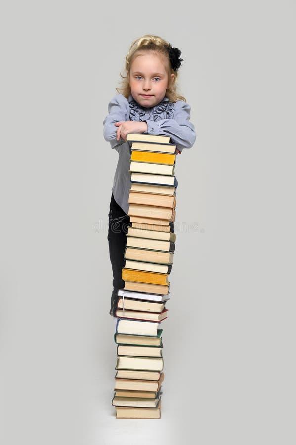 Κορίτσι και μια ψηλή στοίβα των βιβλίων στοκ φωτογραφία