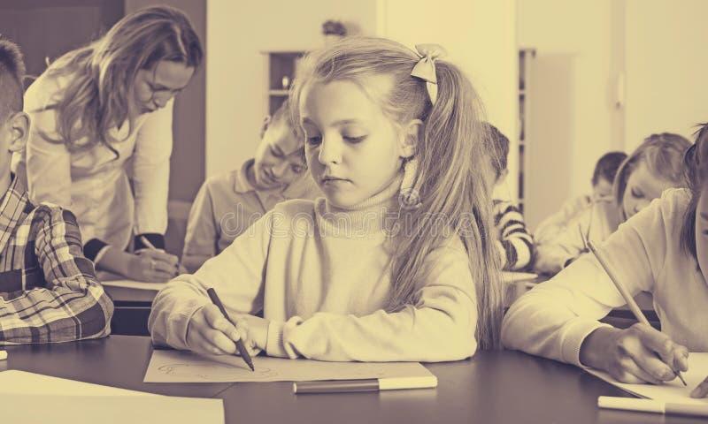 Κορίτσι και παιδιά στη στοιχειώδη ηλικία στο μάθημα σχεδίων στοκ φωτογραφίες