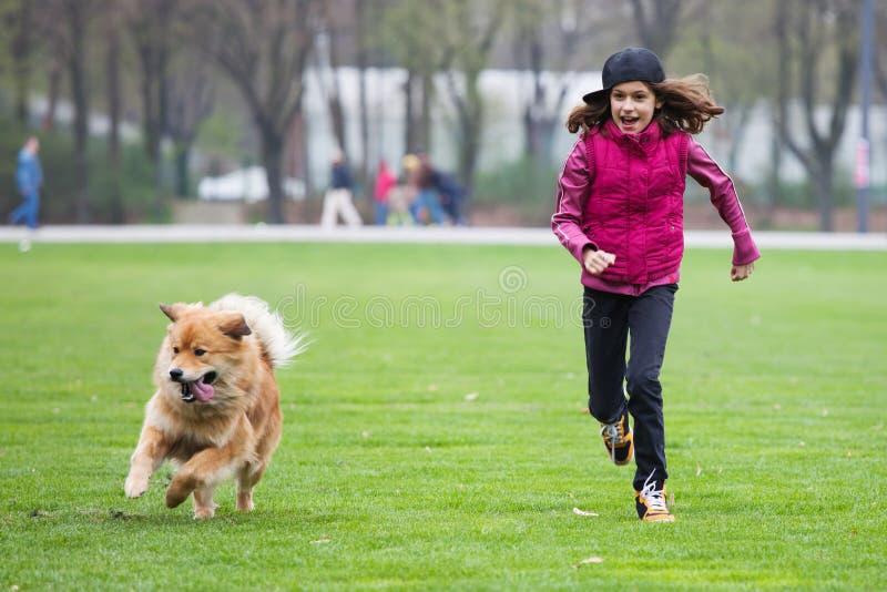 Κορίτσι και σκυλί που τρέχουν στο χορτοτάπητα στοκ φωτογραφία με δικαίωμα ελεύθερης χρήσης