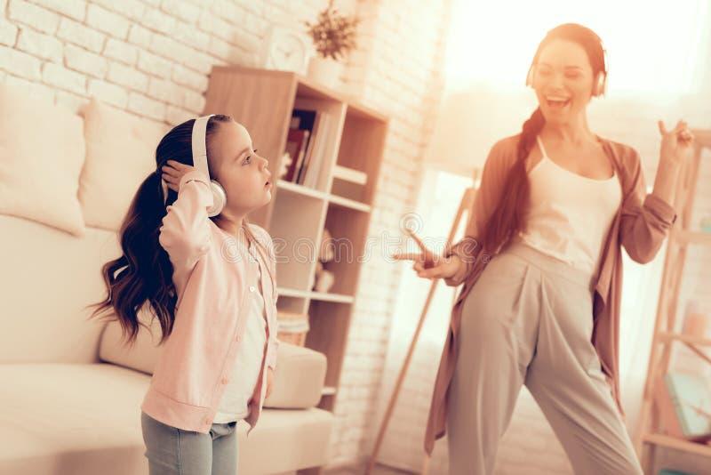 Κορίτσι και χαμογελώντας γυναίκα στις πυτζάμες που χορεύουν στο σπίτι στοκ φωτογραφία με δικαίωμα ελεύθερης χρήσης