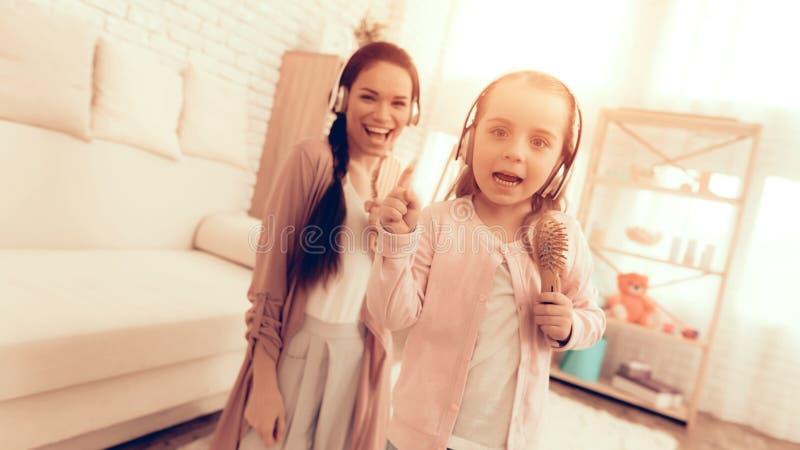 Κορίτσι και Mom στις πυτζάμες που τραγουδούν με τη χτένα στα χέρια στοκ εικόνες με δικαίωμα ελεύθερης χρήσης