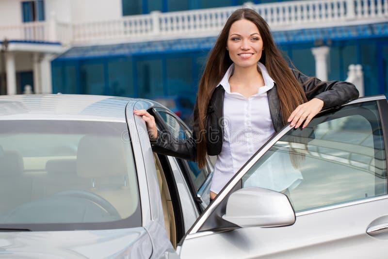 Κορίτσι κοντά στο νέο αυτοκίνητο στοκ εικόνες