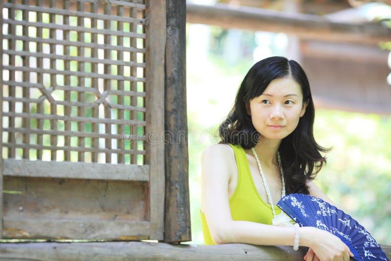 Κορίτσι με έναν ανεμιστήρα από το παράθυρο στοκ φωτογραφίες με δικαίωμα ελεύθερης χρήσης