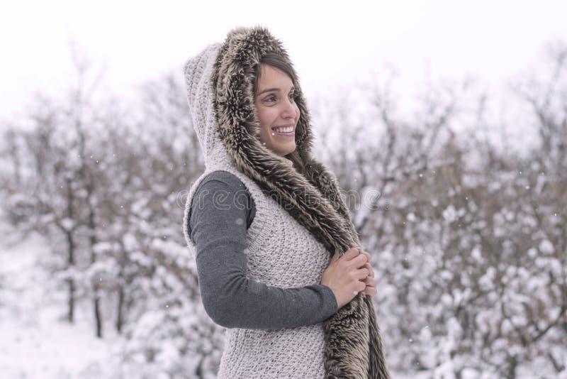 Κορίτσι με ένα με κουκούλα παλτό στο χιόνι στοκ φωτογραφίες