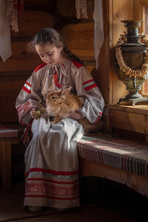 Κορίτσι με ένα κουνέλι, εθνικά ενδύματα, παραδοσιακή ζωή στο σπίτι στοκ φωτογραφία