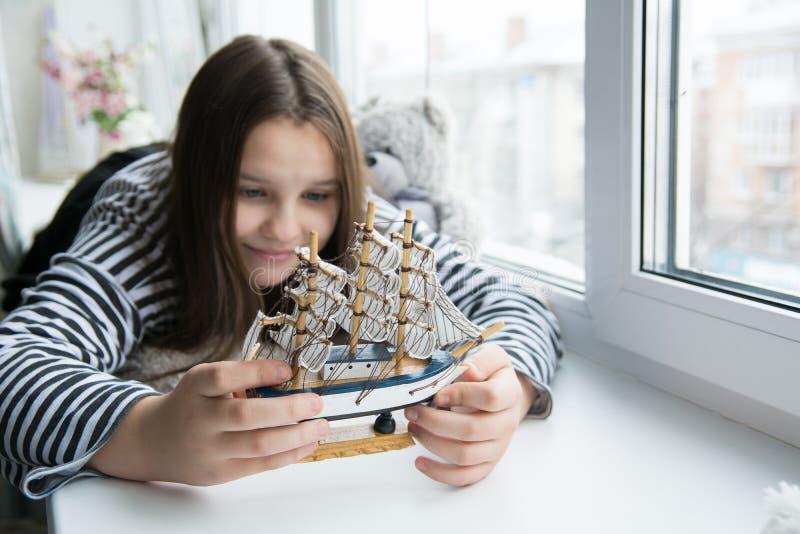 Κορίτσι με ένα σκάφος στη στρωματοειδή φλέβα παραθύρων που ονειρεύεται τα ταξίδια στοκ φωτογραφία με δικαίωμα ελεύθερης χρήσης
