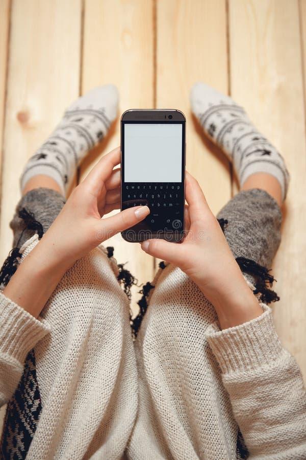 Κορίτσι με ένα τηλέφωνο στα χέρια της στοκ εικόνα