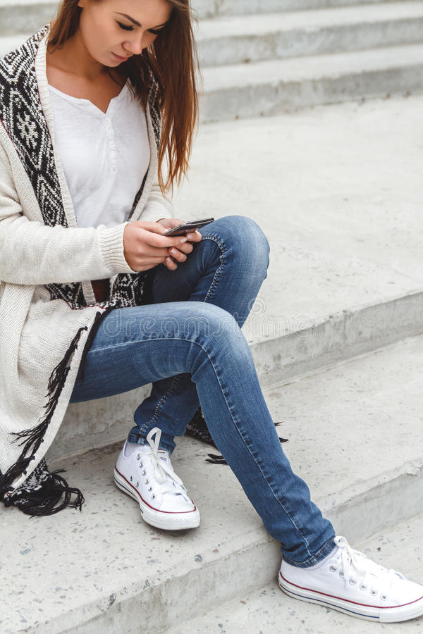 Κορίτσι με ένα τηλέφωνο στα χέρια στοκ φωτογραφία