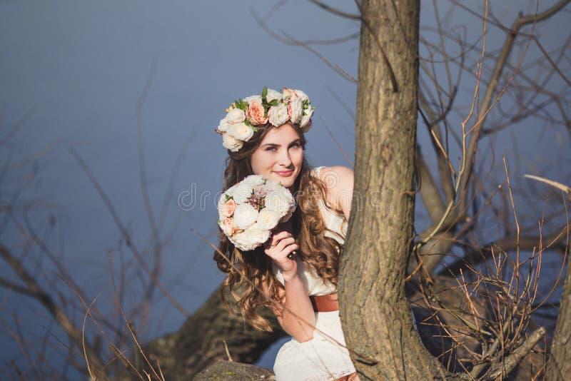 Κορίτσι με ένα floral στεφάνι στην επικεφαλής τοποθέτηση κοντά στο δέντρο στοκ φωτογραφία με δικαίωμα ελεύθερης χρήσης