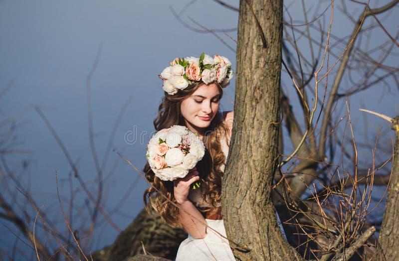 Κορίτσι με ένα floral στεφάνι στην επικεφαλής τοποθέτηση κοντά στο δέντρο στοκ φωτογραφίες με δικαίωμα ελεύθερης χρήσης