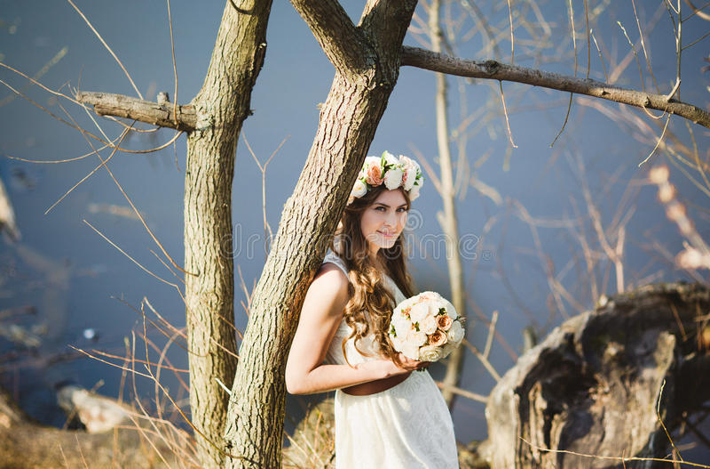 Κορίτσι με ένα floral στεφάνι στην επικεφαλής τοποθέτηση κοντά στο δέντρο στοκ φωτογραφίες