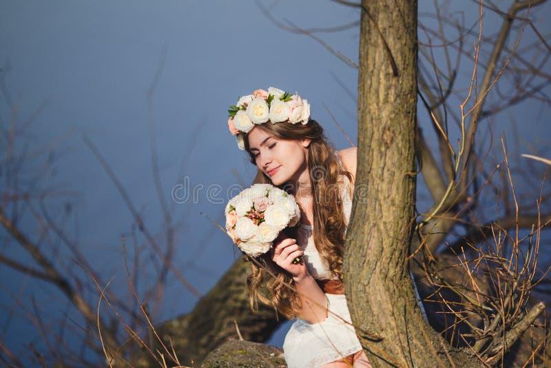 Κορίτσι με ένα floral στεφάνι στην επικεφαλής τοποθέτηση κοντά στο δέντρο στοκ εικόνες