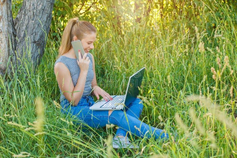 Κορίτσι με ένα lap-top που μιλά στο τηλέφωνο στη φύση στοκ φωτογραφίες με δικαίωμα ελεύθερης χρήσης