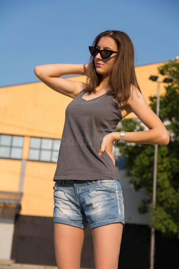 Κορίτσι με γυαλιά ηλίου και καλοκαιρινά ρούχα με το χέρι στο ισχίο και τα μαλλιά ποζάρουν στο πάρκο στοκ εικόνα με δικαίωμα ελεύθερης χρήσης