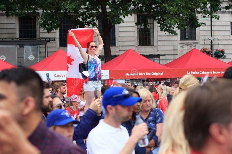 Κορίτσι με μια μεγάλη καναδική σημαία στους εορτασμούς ημέρας του Καναδά στο Λονδίνο 2017 στοκ εικόνες