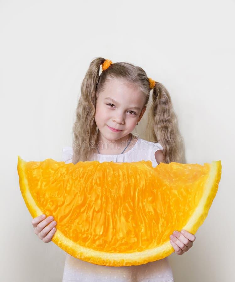 Κορίτσι με μια μεγάλη φέτα του πορτοκαλιού στα χέρια της, ως έννοια για να επιτύχει έναν καλύτερο και περισσότερους στη ζωή στοκ εικόνες