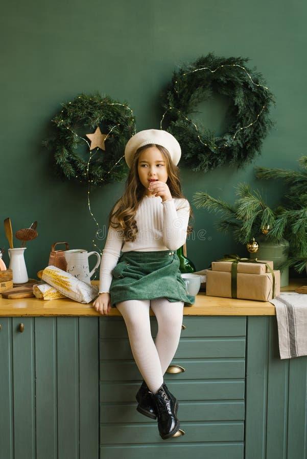 Κορίτσι με μπερέ που κάθεται στην κουζίνα, διακοσμημένο για τα Χριστούγεννα και την Πρωτοχρονιά και τρώει μπαγκέτα στοκ φωτογραφίες
