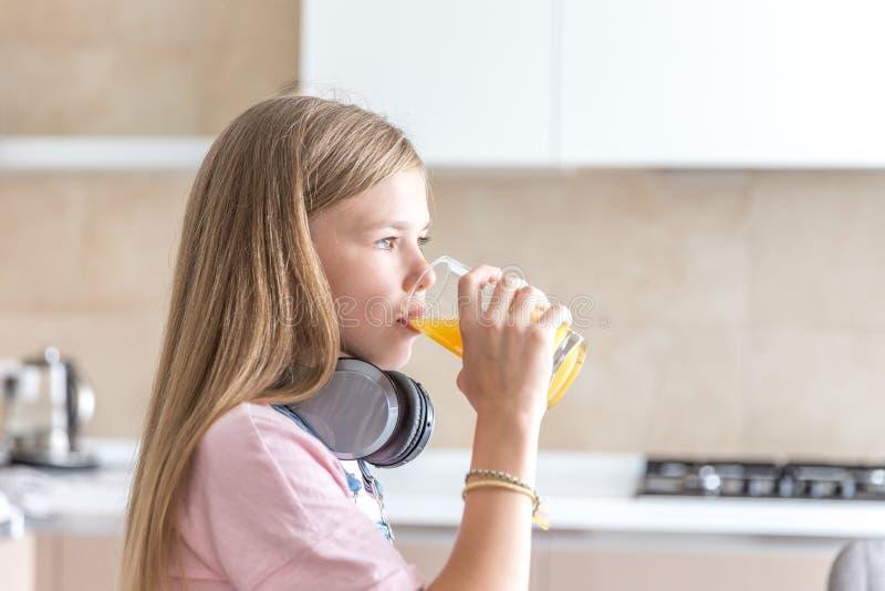 Κορίτσι με τα ακουστικά που πίνει το χυμό από πορτοκάλι στην κουζίνα στοκ φωτογραφία με δικαίωμα ελεύθερης χρήσης