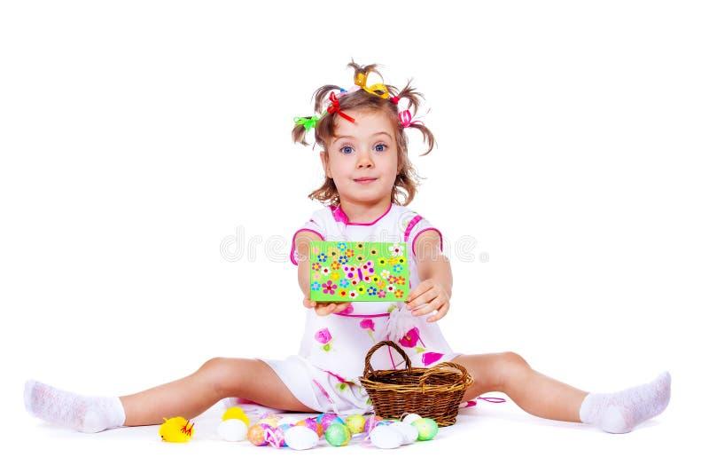 Κορίτσι με τα αυγά Πάσχας και τη ευχετήρια κάρτα στοκ εικόνες