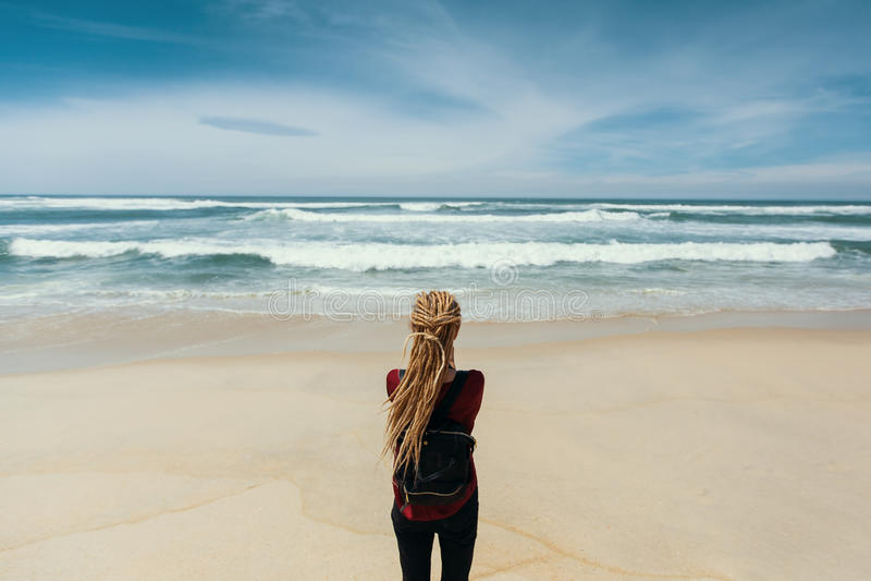 Κορίτσι με τα ξανθά dreadlocks που στέκονται στην ακτή που προσέχει τον ωκεανό Ταξίδι στοκ φωτογραφία