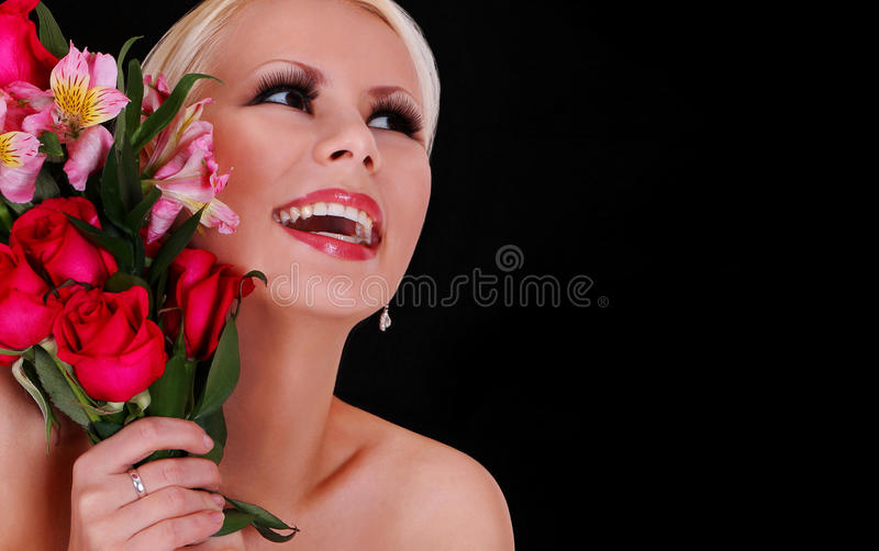 Κορίτσι με τα τριαντάφυλλα. ευτυχής νέα γυναίκα με την ανθοδέσμη των λουλουδιών πέρα από το μαύρο υπόβαθρο, όμορφο ξανθό χαμογελών στοκ φωτογραφία