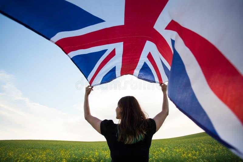 Κορίτσι με τη βρετανική σημαία στον πράσινο τομέα στοκ φωτογραφία