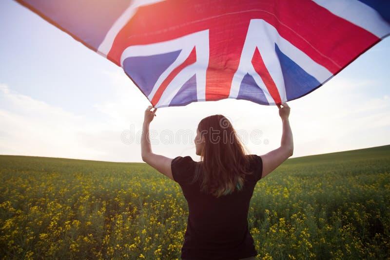 Κορίτσι με τη βρετανική σημαία στον πράσινο τομέα στοκ εικόνες