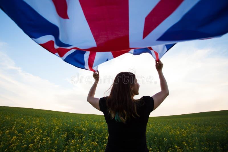 Κορίτσι με τη βρετανική σημαία στον πράσινο τομέα στοκ εικόνα