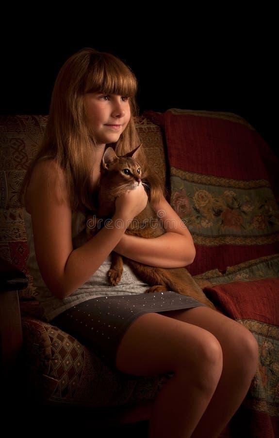 Κορίτσι με τη γάτα, στο εσωτερικό. Συγκρατημένος. στοκ εικόνες με δικαίωμα ελεύθερης χρήσης