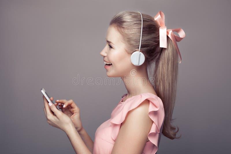 Κορίτσι με τη μουσική ακούσματος ακουστικών και κατοχή της διασκέδασης στοκ φωτογραφίες