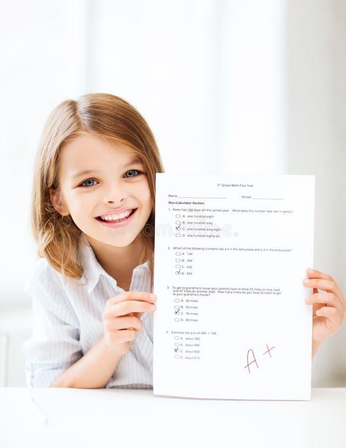 Κορίτσι με τη δοκιμή και το βαθμό στο σχολείο στοκ εικόνα με δικαίωμα ελεύθερης χρήσης