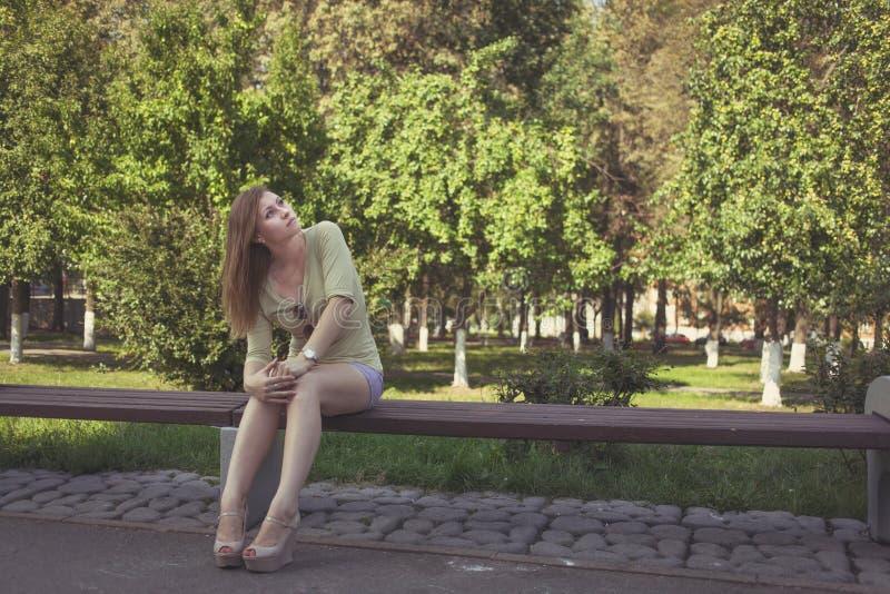 Κορίτσι με τη ρέοντας τρίχα στα κοντά σορτς και παπούτσια με τα τακούνια που κάθονται σε έναν πάγκο στοκ φωτογραφίες