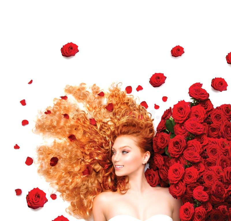 Κορίτσι με τη σγουρή κόκκινη τρίχα και τα όμορφα κόκκινα τριαντάφυλλα στοκ φωτογραφία