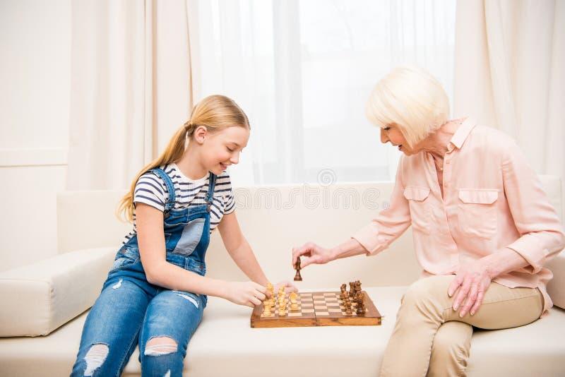 Κορίτσι με τη συνεδρίαση γιαγιάδων στον καναπέ και το σκάκι παιχνιδιού στοκ φωτογραφίες με δικαίωμα ελεύθερης χρήσης